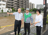 一時、「氾濫危険水位」を超えた境川を視察する小磯都議ら=22日 東京・町田市