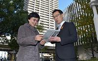 公明新聞の記事について、党員の松丸美枝さんと語り合う丸山議員=東京・港区