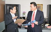 若松謙維参院議員(左)はオフィス機器販売会社の会長に「国の支援をビジネスチャンスに」と語り、調査を進めた=4日 福島・郡山市