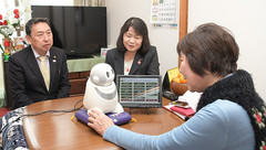 Ms. Fujita (right) talks to her attendant robot with assembly members Kido and Ochi.