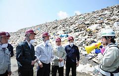 災害がれきの2次処理場で説明を受ける山口代表と井上幹事長ら=24日 宮城・石巻市