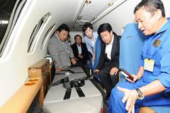 救急搬送用の小型ジェット機内で説明を聞く、いなつ氏と古屋、渡辺氏ら=30日 札幌市