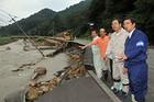 河川の氾濫で削られた県道を視察する山本(博)、斉藤氏ら=29日 山口市阿東