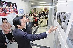 山口代表の案内で写真パネルを見て回る参加者=21日 党本部
