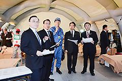 船内の仮設診療所で担当者から説明を聞く長沢、平木氏ら=25日 東京・晴海ふ頭