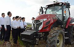 ロボットトラクターの作業状況を調査する中川氏(左から2人目)ら=19日 福井市