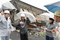吉村町議(右端)から被害状況を聞く井上幹事長(左から2人目)ら=21日 熊本・益城町