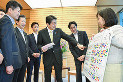 VAのボードを見ながら若者の代表と懇談する安倍首相と山口代表、石川青年委員長ら=11日 首相官邸