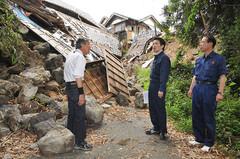 倒壊した住宅にふさがれた町道を視察する濱地氏ら=21日 熊本・御船町