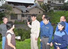 自宅の屋根が飛ばされた松戸さんから被害状況を聞く平木氏と角田氏ら=22日 千葉・南房総市