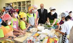 親子料理教室で子どもたちが食事を作る様子を見守る山本市議(右から4人目)