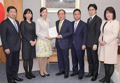 菅官房長官(中央)に中間提言を手渡す党プロジェクトチームのメンバー=15日 首相官邸