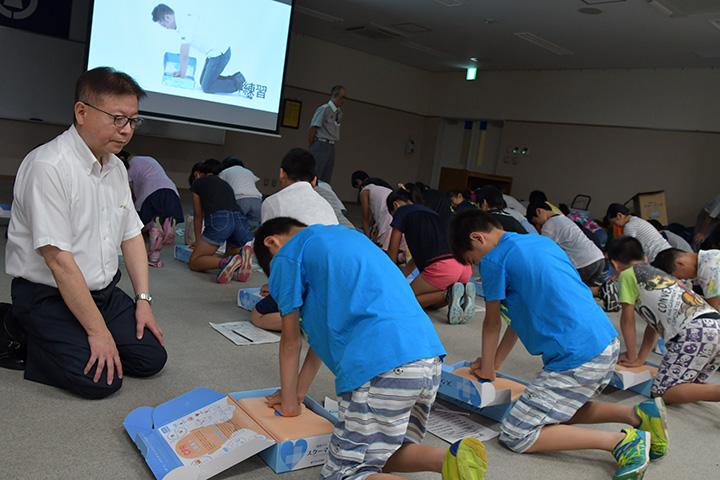 胸骨圧迫に取り組む小学生たちを見守る佐藤市議(左端)