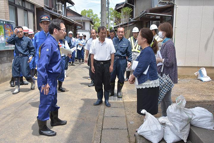 家屋の後片付けに追われる高野川流域地区の住民を励ます竹内氏(手前左)=9日 京都・舞鶴市