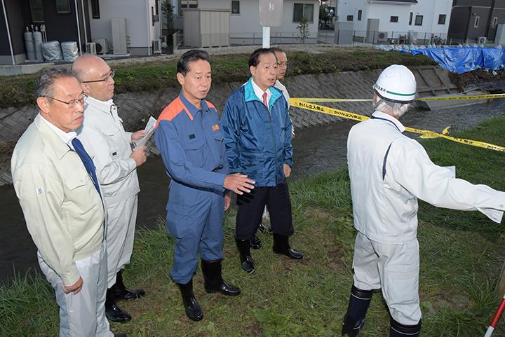 大森川が越水した現場を視察する太田議長と、いとう県議=15日 福島市