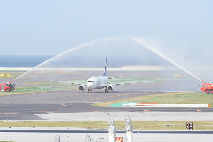 放水アーチで歓迎される第2滑走路「第1便」の旅客機=26日 那覇空港