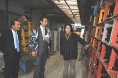 ごみステーション内で、リサイクル製品を着て事業内容を視察する谷あい氏(ら