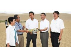 鳥取砂丘でスタッフから地層などについて説明を受ける谷合氏(中央)ら