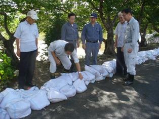 土のうを積み上げた笹ヶ瀬川の堤防を調査する谷合議員ら