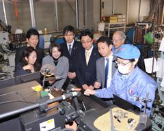 工場内で金属の加工作業を視察する谷合委員長ら